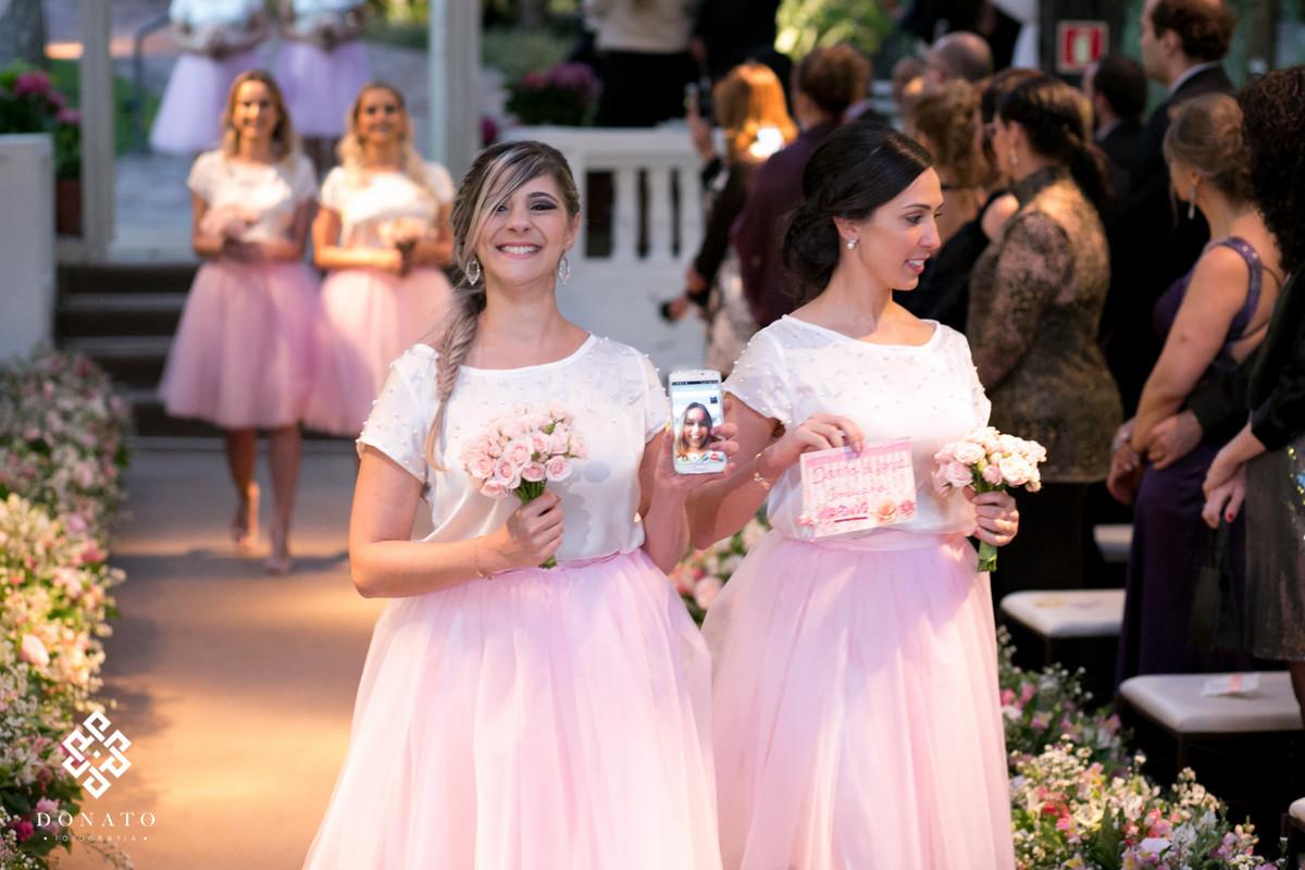 dama entra com o celular na mão, fazendo um live do casamento para a amiga que não pode vir e era madrinha.
