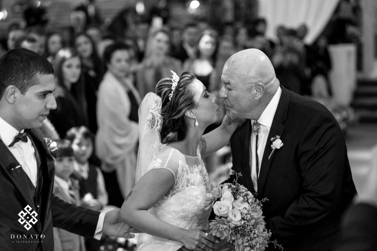 Pai da beijo na noiva na entrada da cerimônia.