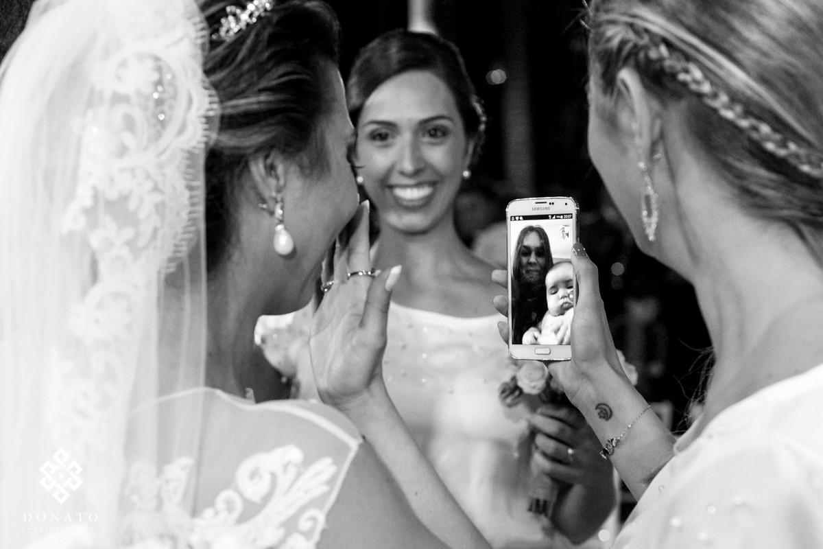 Noiva se emociona ao ver a amiga no celular, a imagem vem dos EUA, via um video chamada.