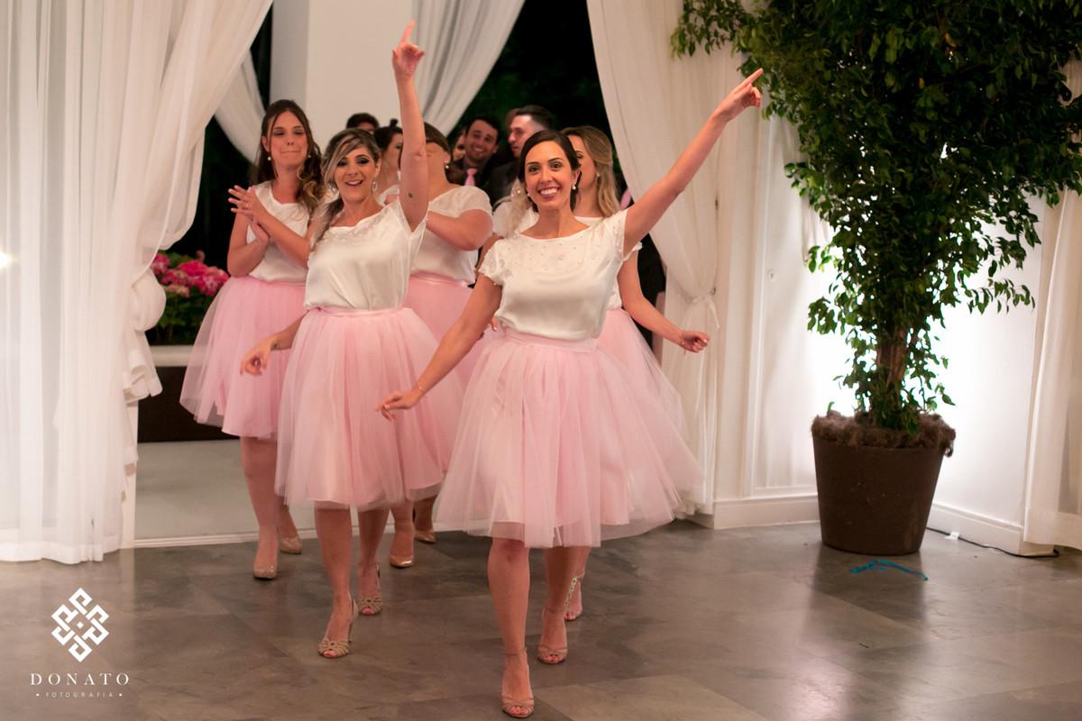 Damas entram no salão fazendo uma grande festa.