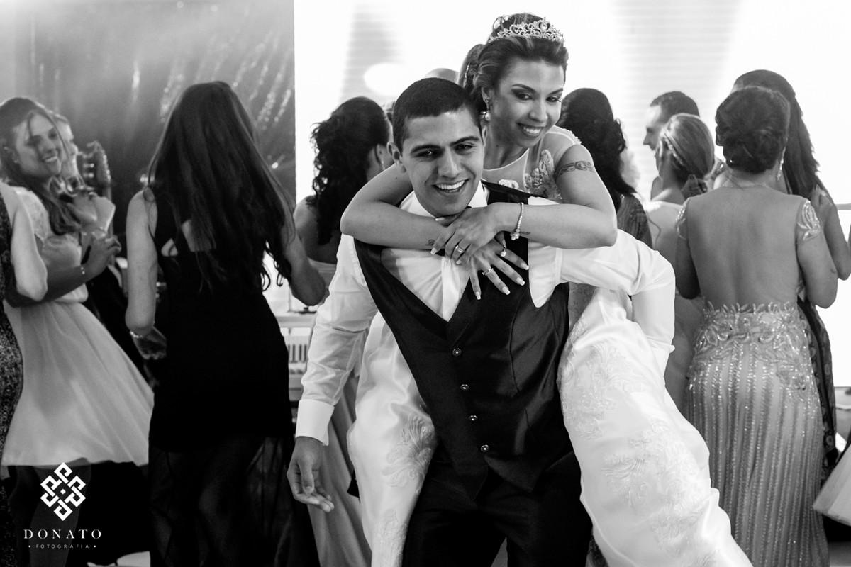 Noiva sai de cavalinho no noivo, os dois se divertem na pista de dança.