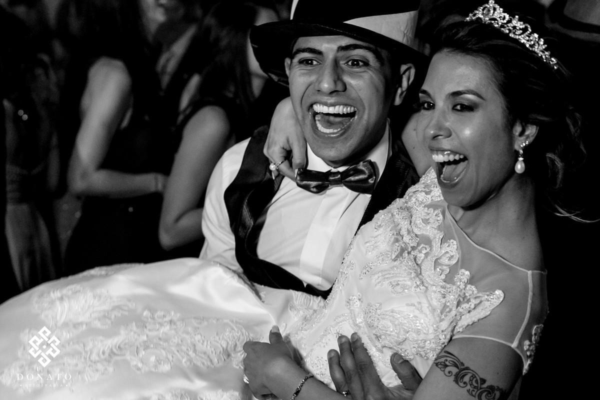 Noivo pega a noiva no colo e se diverte junto com os amigos.