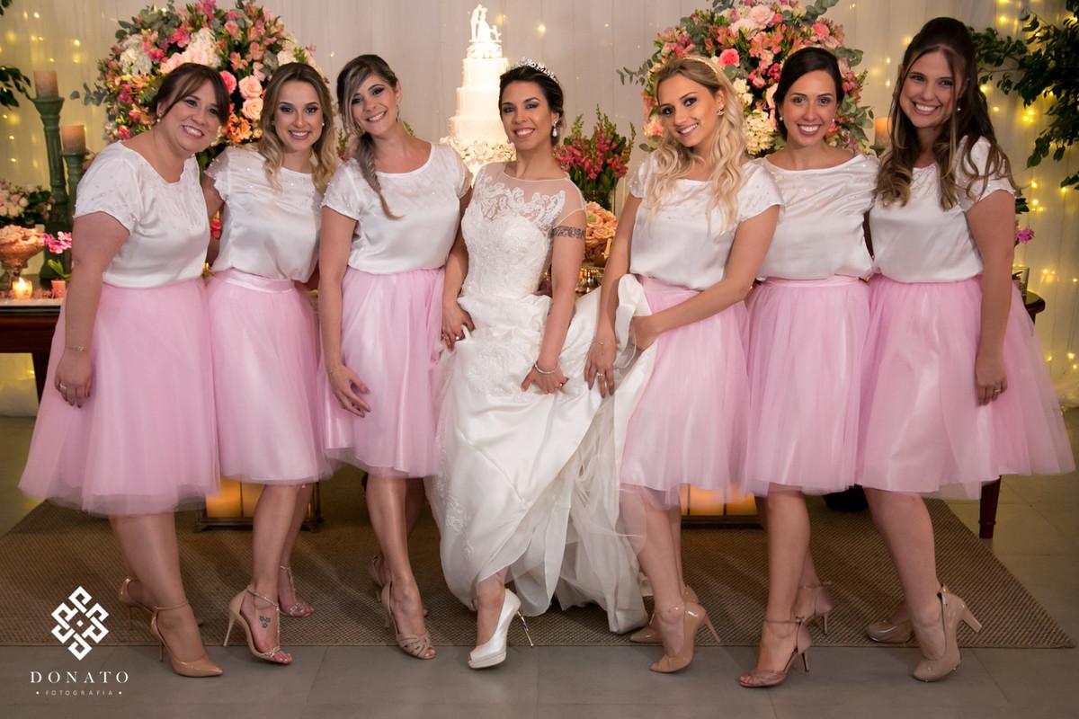 Madrinhas todas com vestidos cor de rosa fazem foto com a noiva, e fica um bonito contraste de cores..