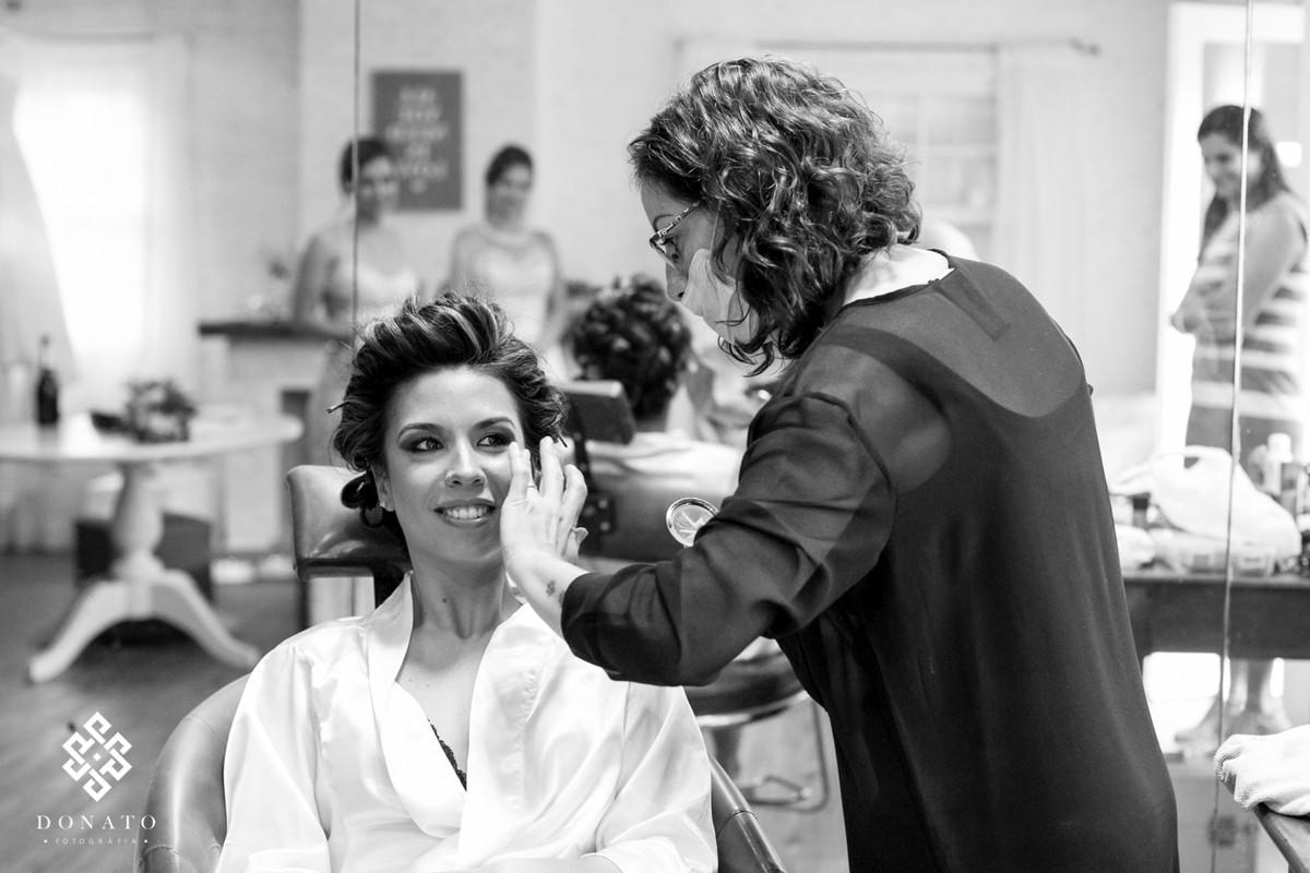 Maquiadora esta preparando a makiagem da noiva para casamento.