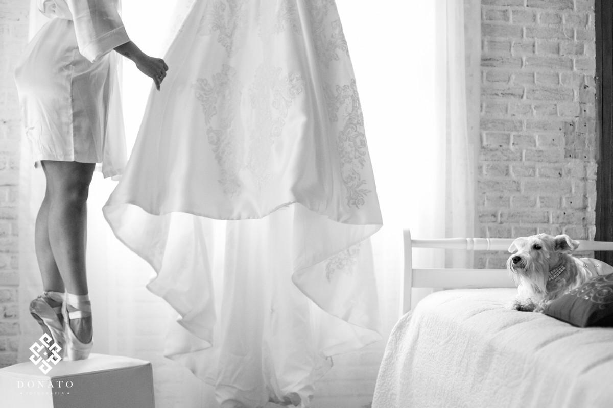 Retrato da noiva arrumando seu vestido, ao lado o seu cachorro olhando tudo.