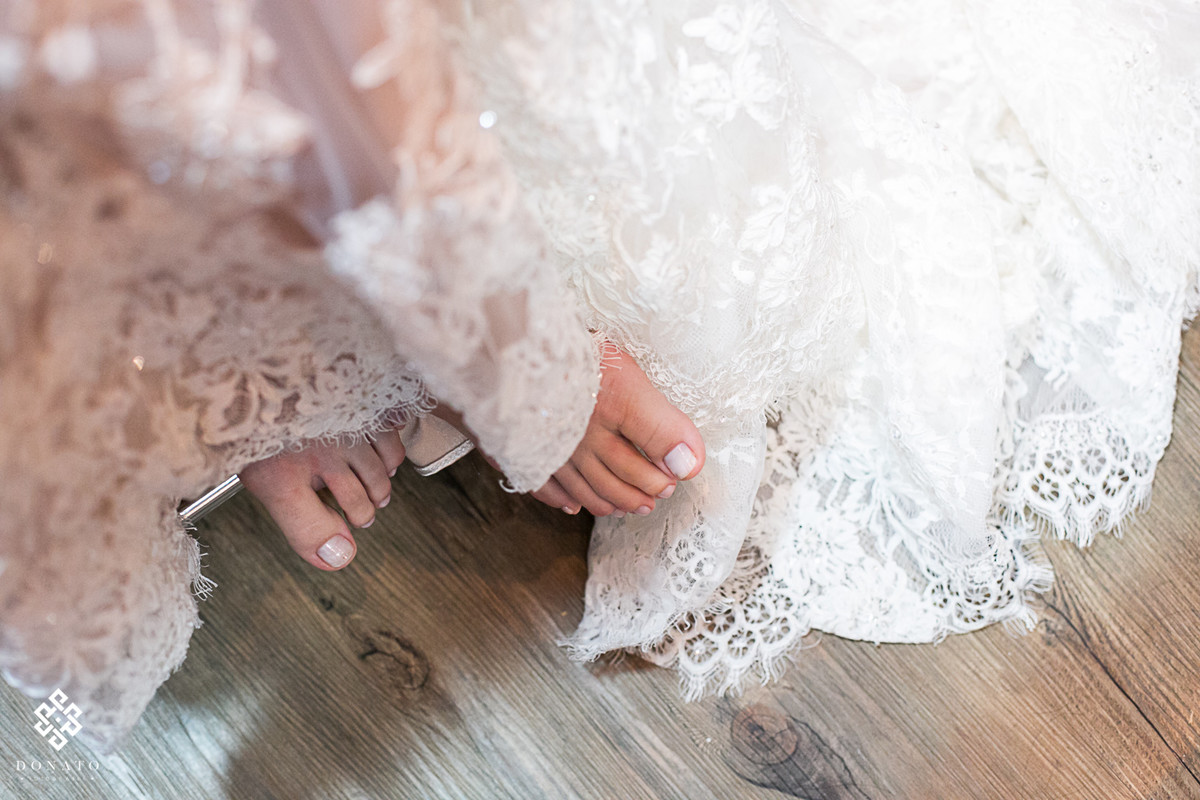 detalhes dos pes da noiva e a barra do vestido.
