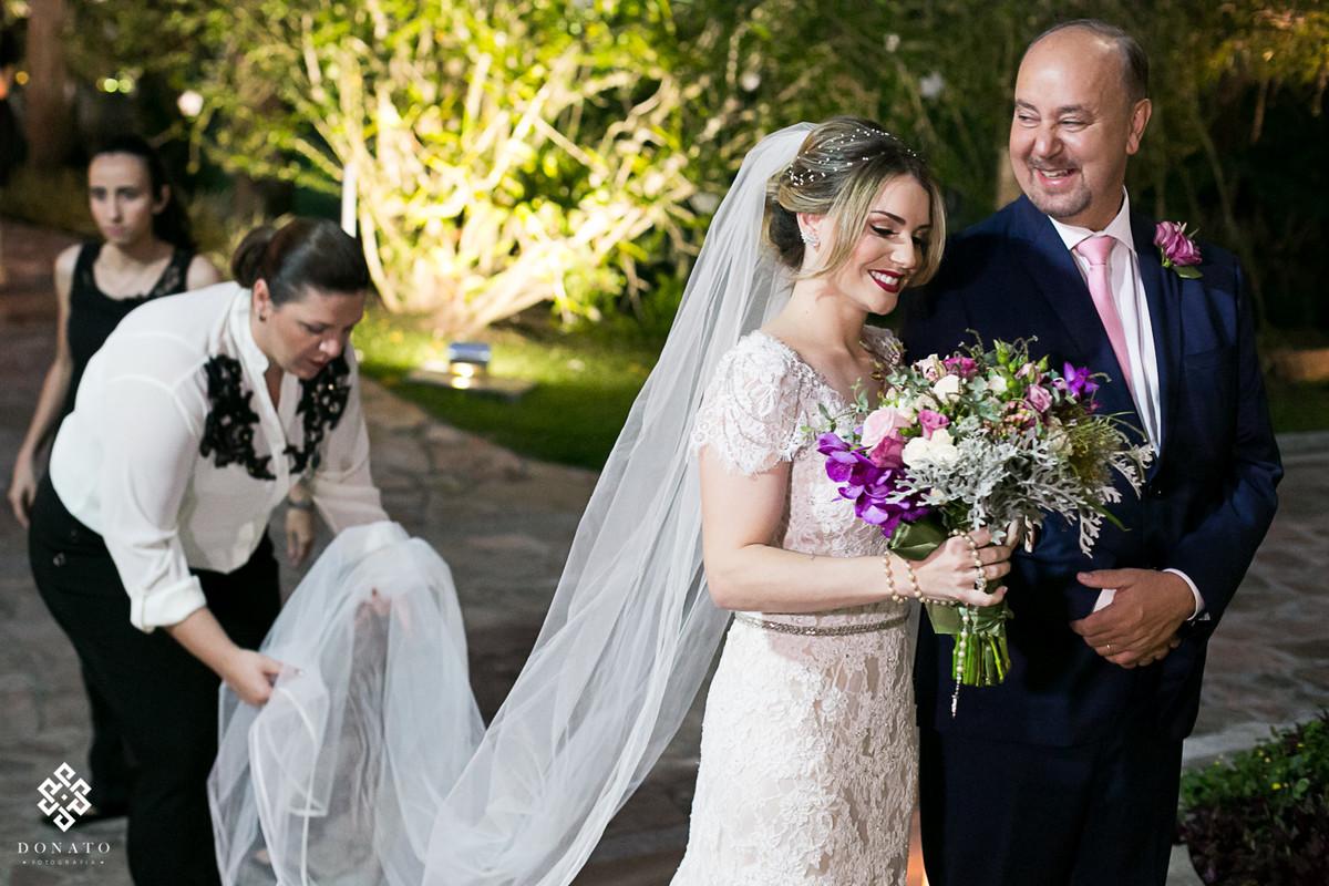Noiva e pai, se preparam para entrada enquanto a assessora da na barra do meu vestido arruma a cauda do vestido ca noiva.