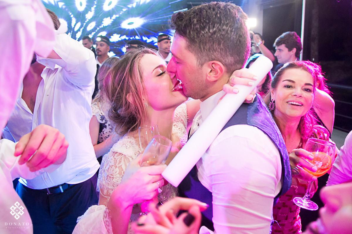 Noiva beija o noivo na pista de dança.