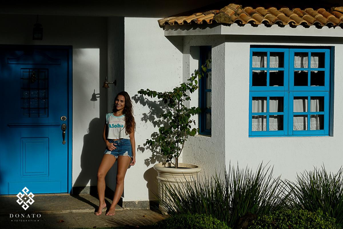 foto da debutande para o seu 15 anos, em frente a uma casa azul e brando.