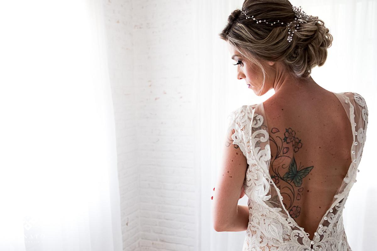 Noiva deixa a mostra a tatuagem nas costas ao fechar o vestido Lucas Anderi.