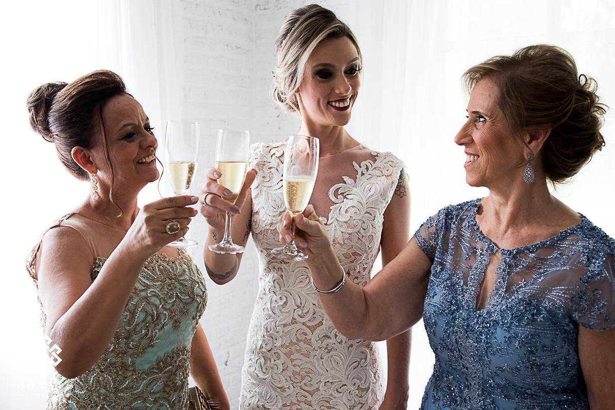 Noiva brinda com a mãe e sogra na sala da noiva da fazenda 7 lagoas.