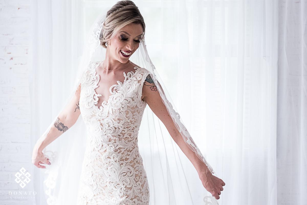 Noiva Carol meche no veu do vestido do Lucas Anderi.