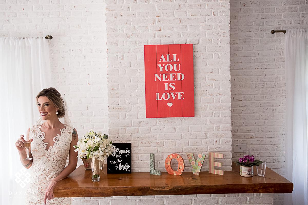 """Retrato da noiva com a taça a mão, com imagem tradicional do poster da Fazenda 7 Lagoas, onde diz """"All You Need Is Love""""."""