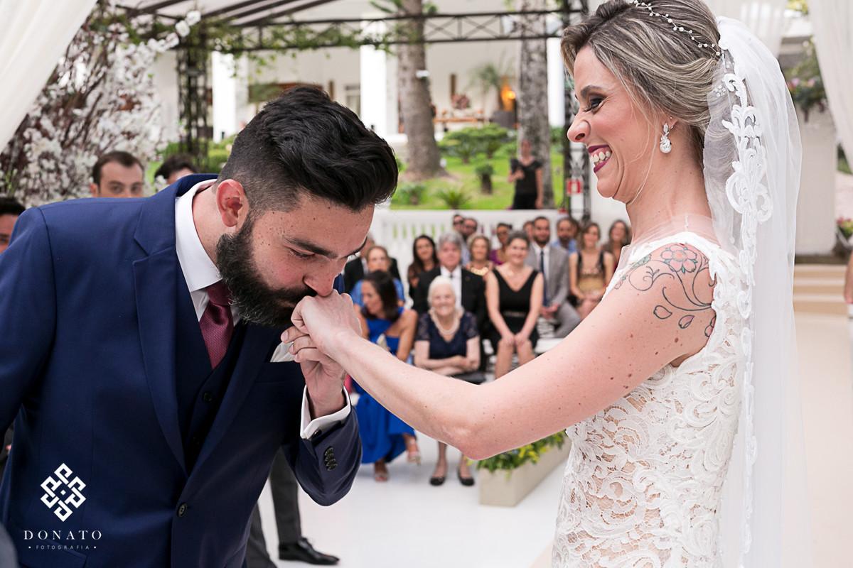 Noivo beija a mão da noiva na troca das alianças.