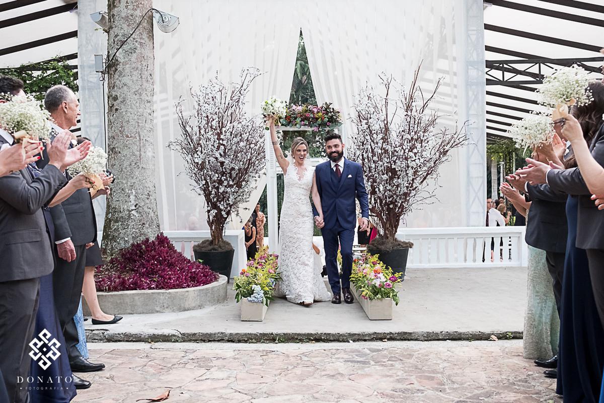 Noivos saem e comemoram o casamento.