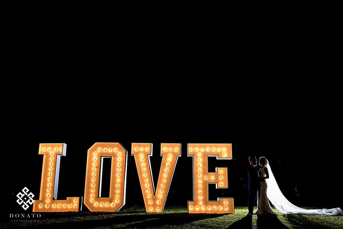 Foto do letreiro gigante escrito Love, todo aceso com led, na foto tem os noivos ao lado do letreiro.