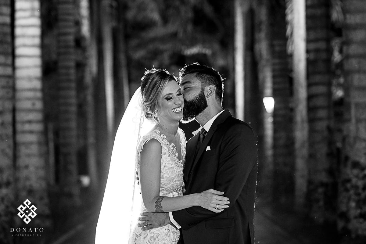 Noivos dao um beijo na entrada da fazenda 7 lagoas entres as enormes palmeiras centenárias.