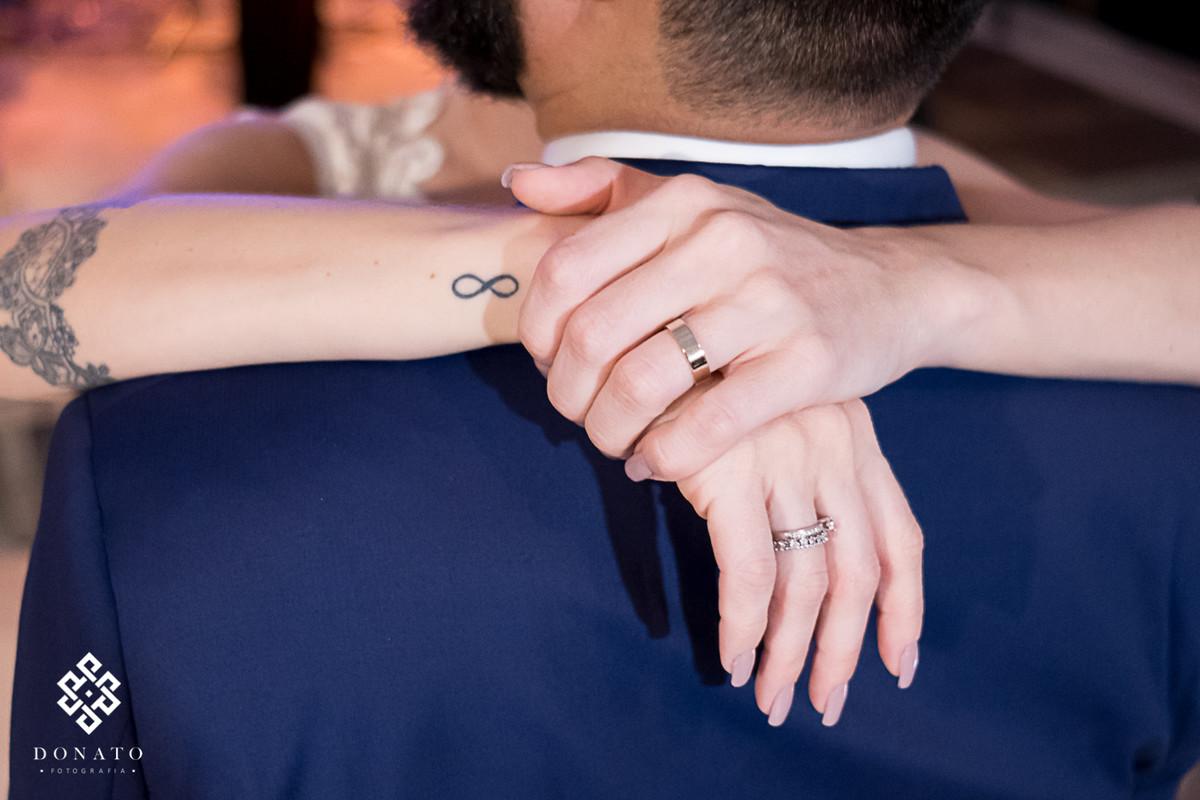 Detalhe das mão da noiva no ombro do noivo.