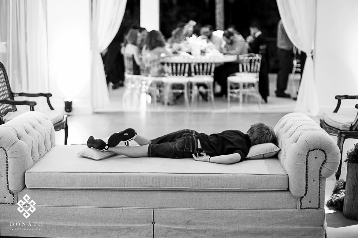 Menino dorme no sofá da fazenda enquanto a festa continua.
