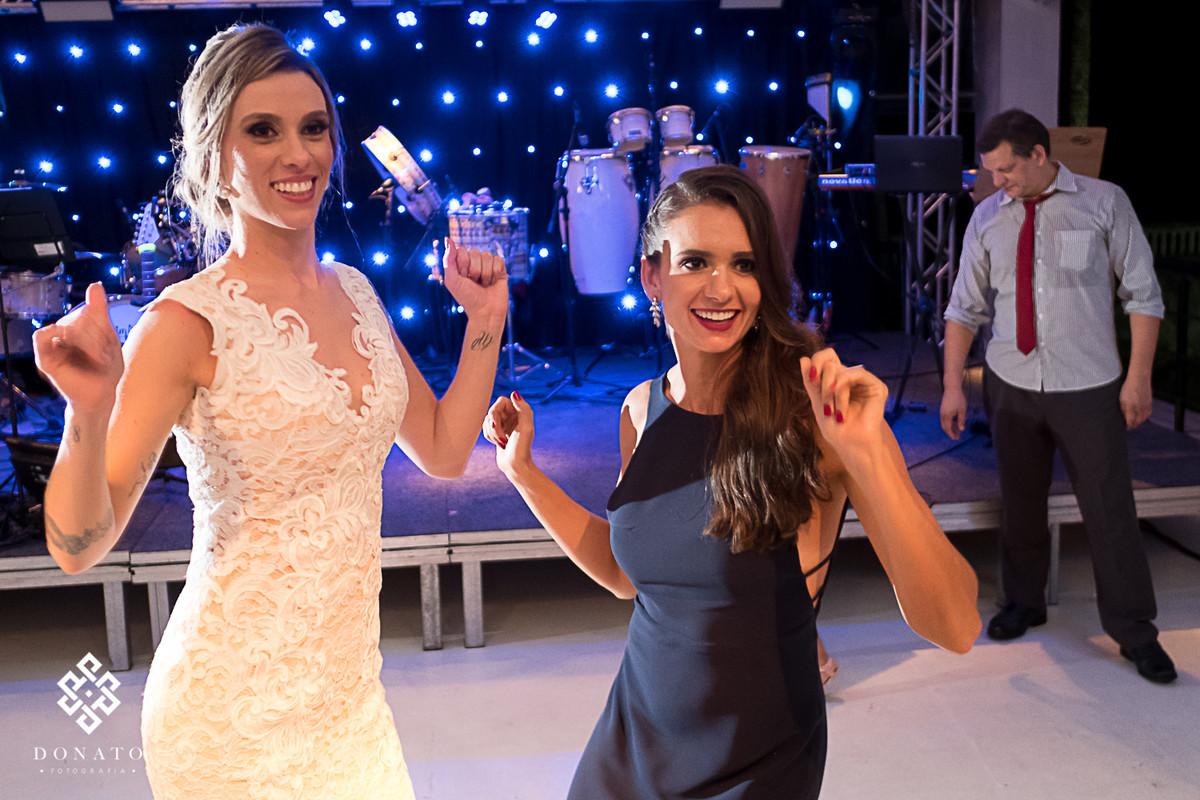 Noiva e amiga dançam no salão da Fazenda 7 Lagoas.