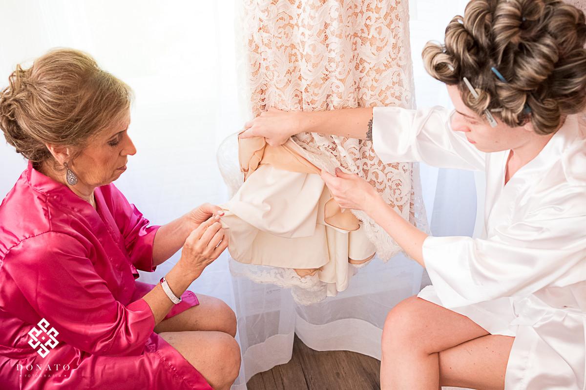 Mae e noiva colocam pingente na barra do vestido Lucas Anderi.