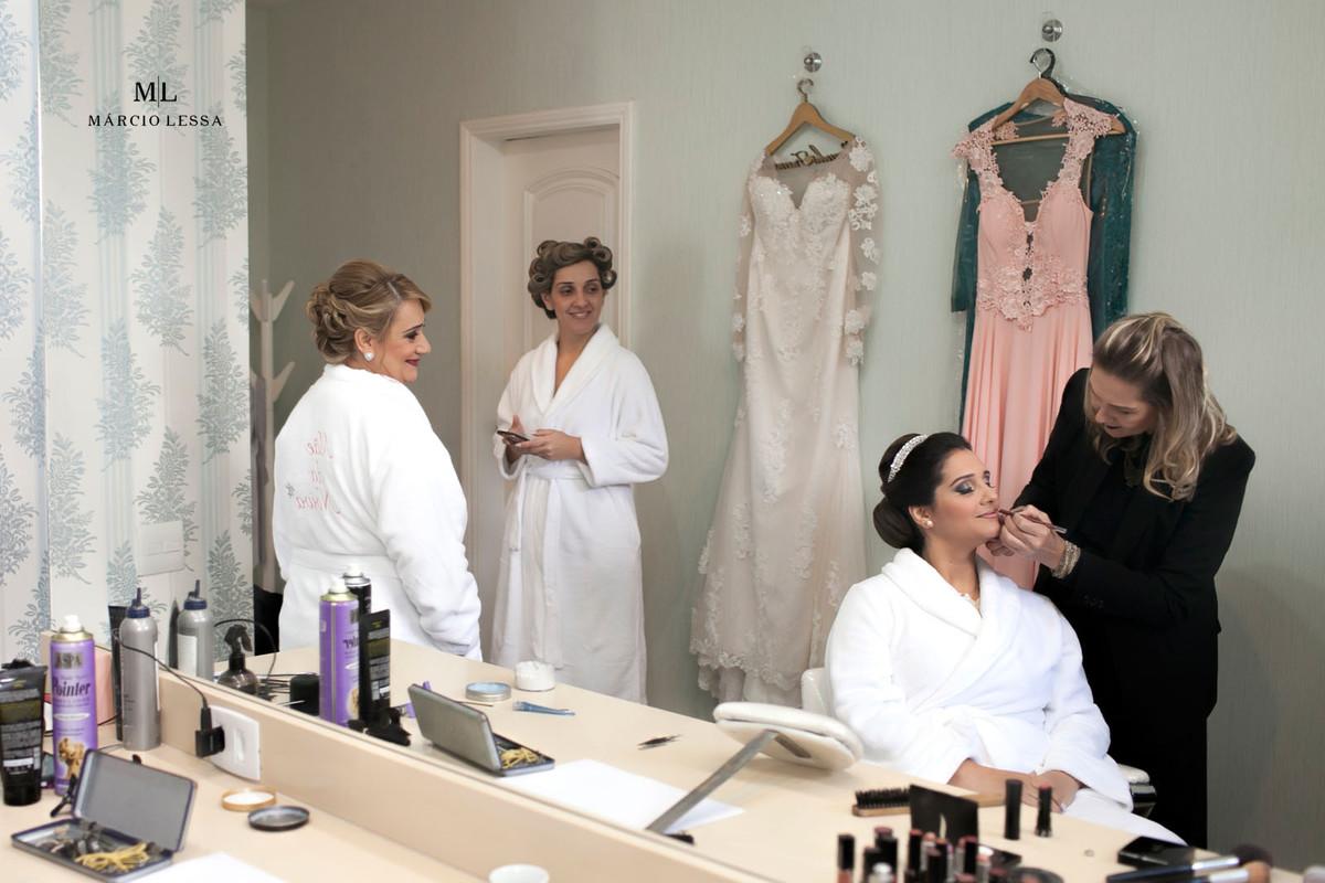 Mãe e irmã observando a noiva na maquiagem