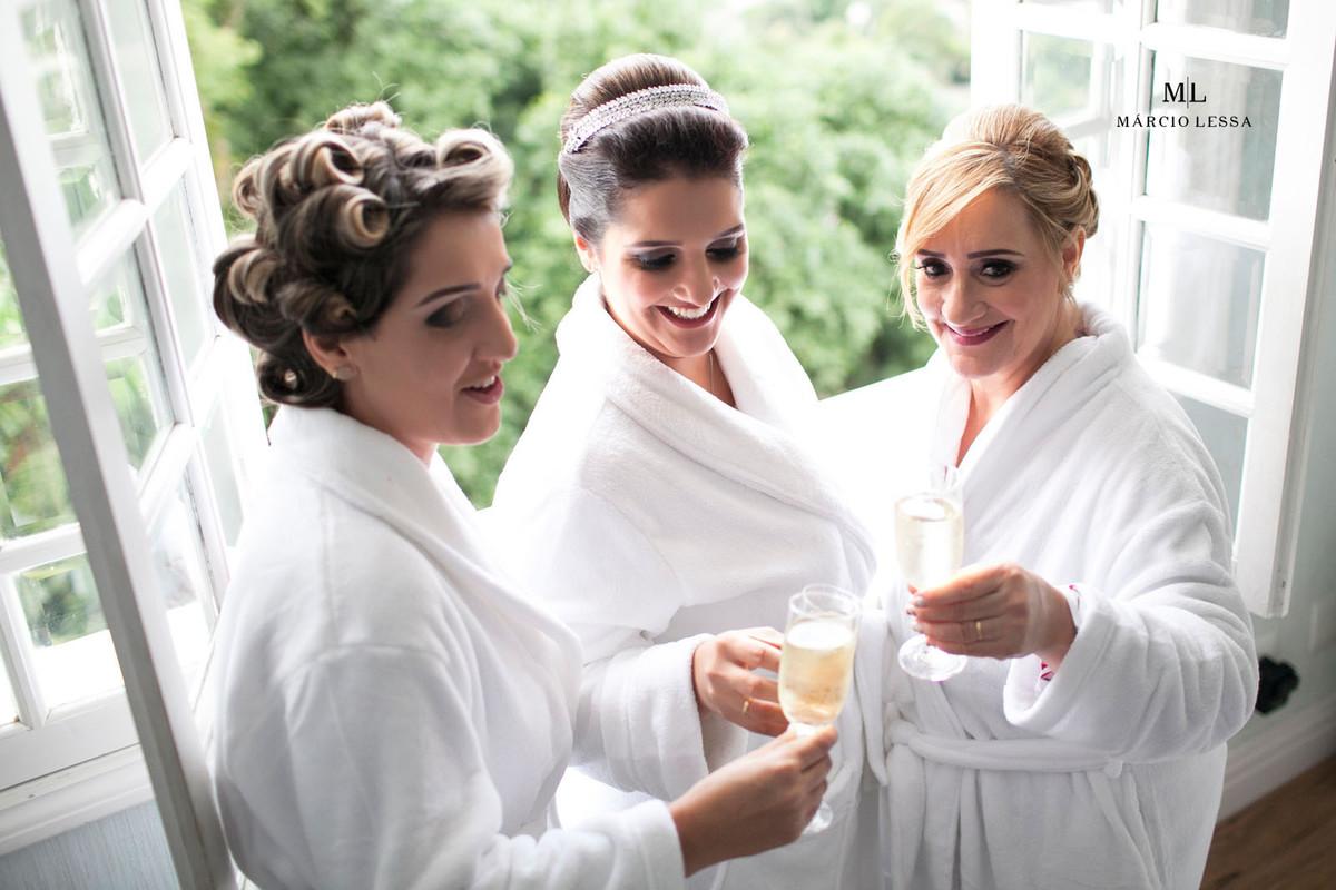 A noiva com sua mãe e irmã celebrando com champanhe