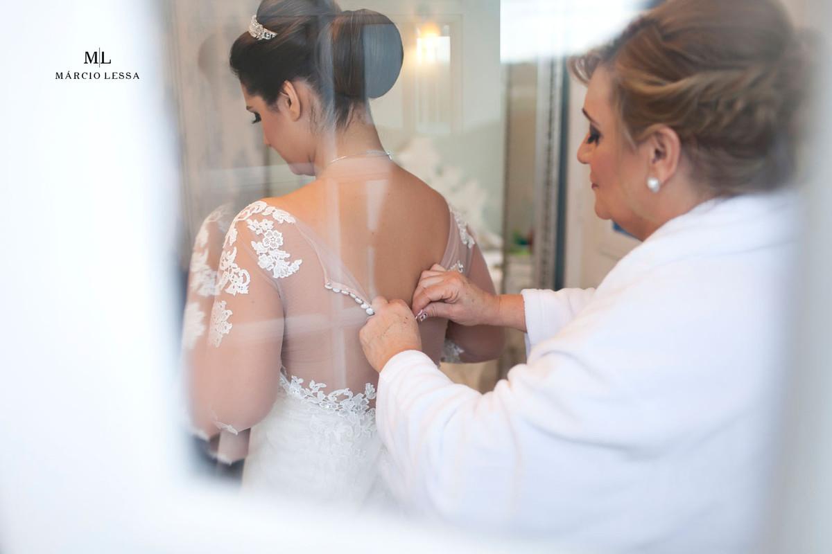 Mãe da noiva fechando o vestido da noiva
