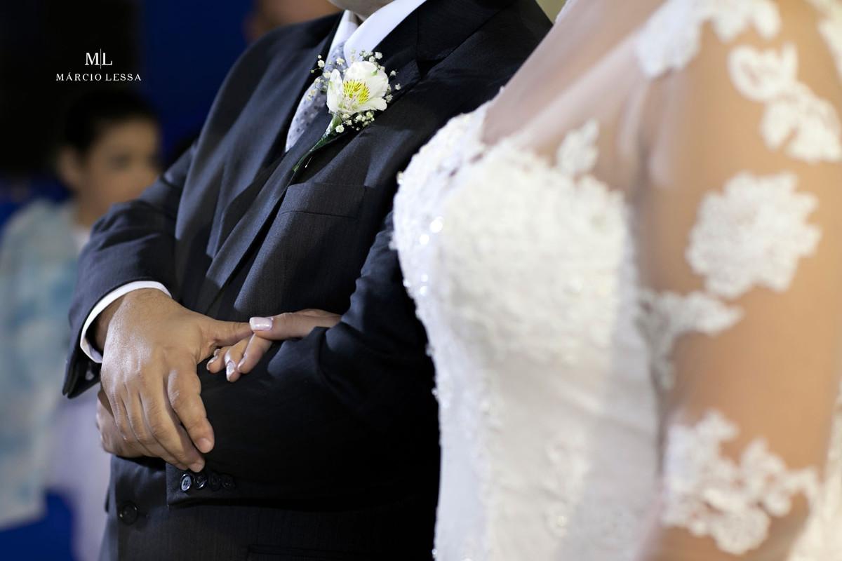 Detalhes das mãos dos noivos e da flor na lapela do noivo