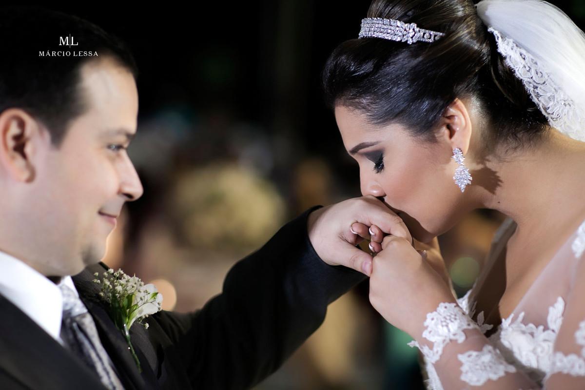 Linda fotografia da noiva beijando a mão do noivo