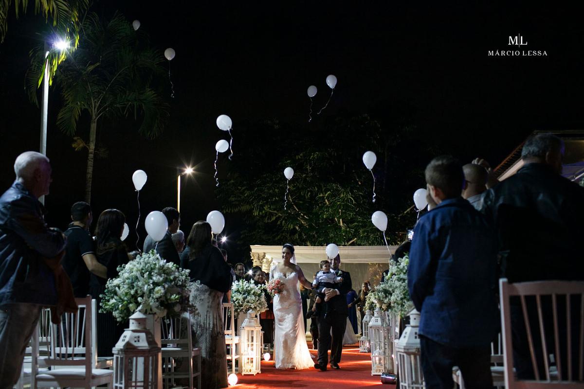 A saída dos noivos e bolas brancas voando ao sabor dos ventos