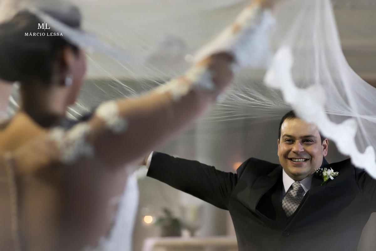 O noivo brincando com o véu da noiva