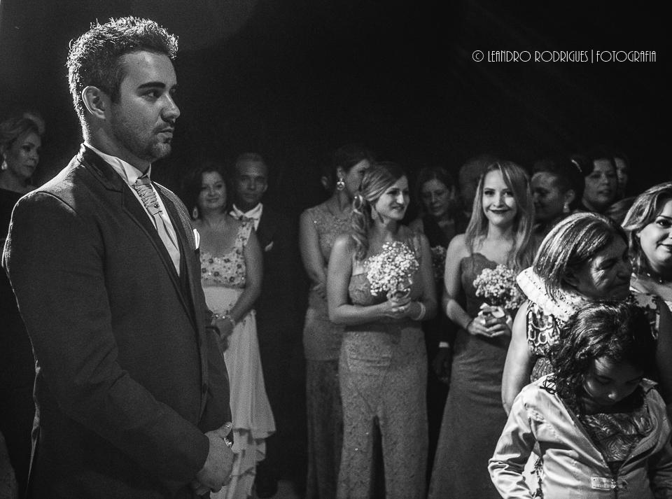 Noivo olhando a noiva entrar, atras convidados