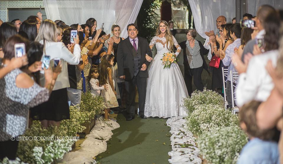 noiva entrando para a cerimonia junto com o pai e convidados ao lado