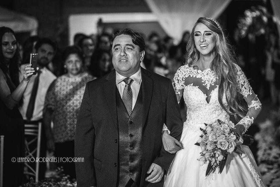 Noiva sorrindo ao ver o noivo na entrada junto com o pai