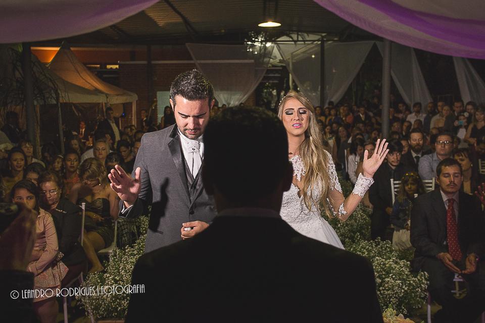 noivos com as mãos erguidas fazendo a oração junto com o pastor