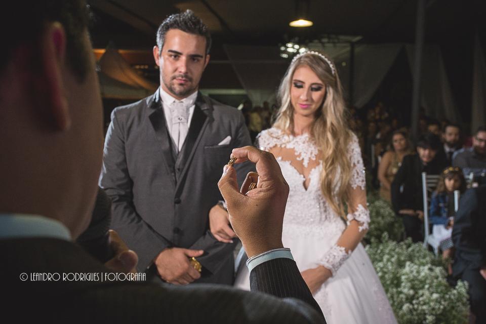pastor com a mão direita erguida segurando aliança, noivos olhando para a aliança