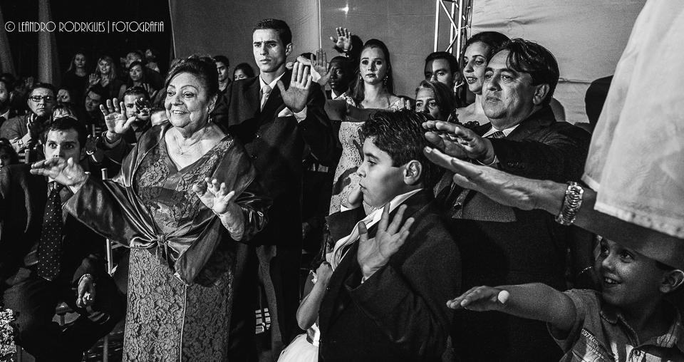 padrinhos orando com o braço esticado em direção aos noivos