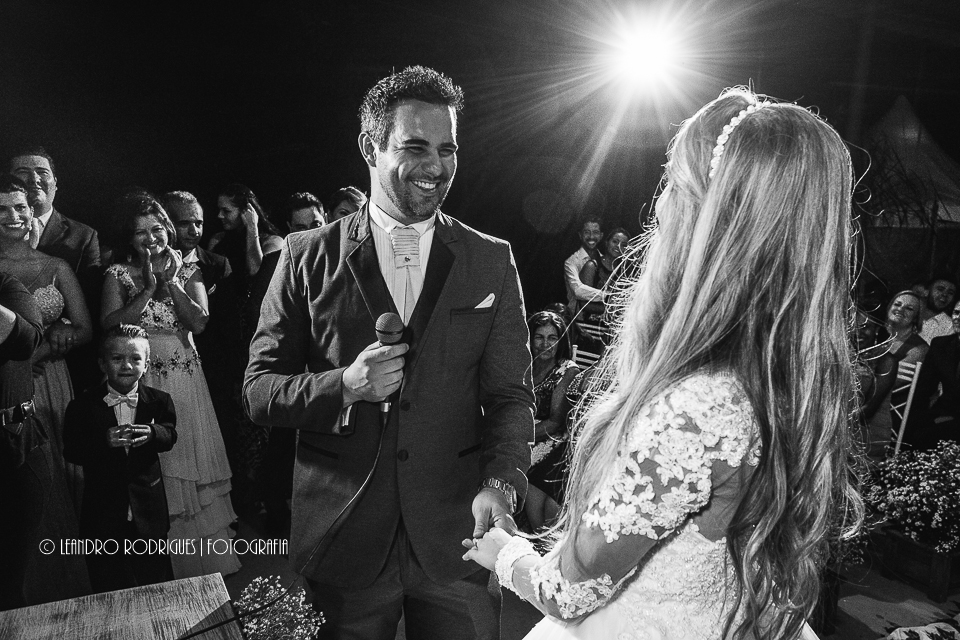 noivo segurando o microfone de frente para a noiva e sorrindo