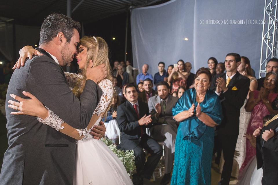 noivo beijando a noiva e convidados batendo palmas