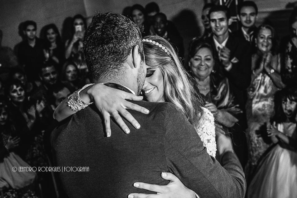 noiva abraçando o noivo e padrinhos no fundo