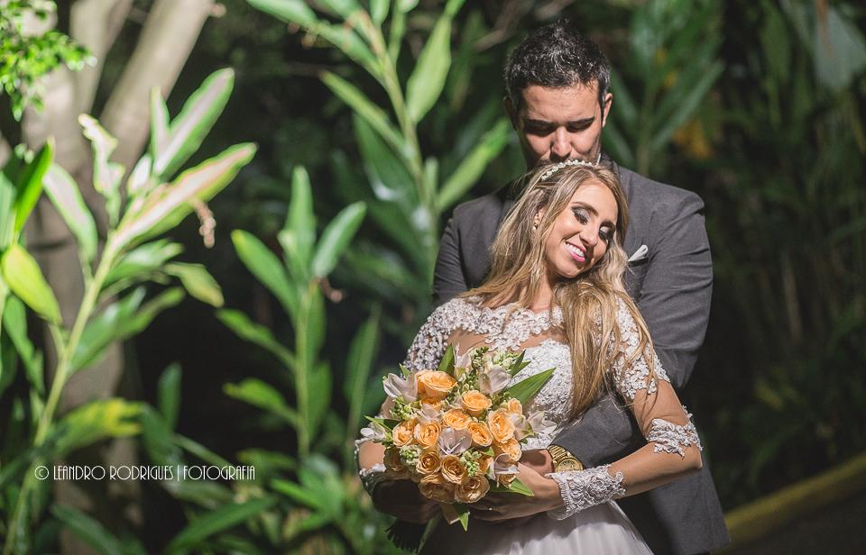 noivo abraçando a noiva por trás e beijando a cabeça da noiva que etá segurando o buquê com as duas mãos