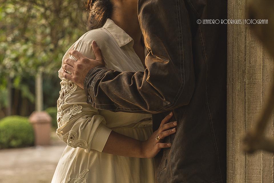 Noivos um de frente para o outro, noiva com a mão na cintura do noivo e ele com a mão no ombro dela