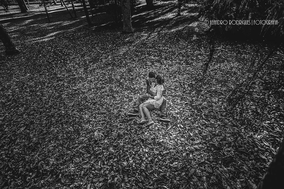 Noivos sentados nas folhas secas e se abraçando