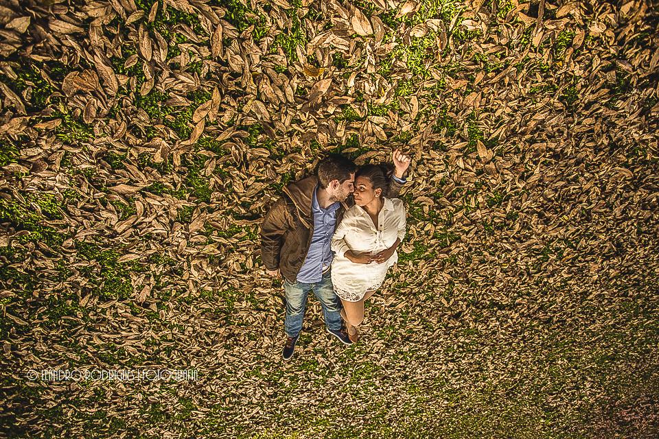 Noivos deitados com as testas encostadas na grama com folhas secas