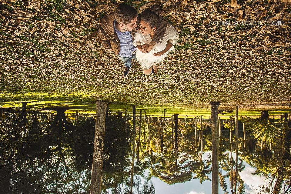 Noivos deitados abraçados no chão muitas folhas secas  e de fundo arvores