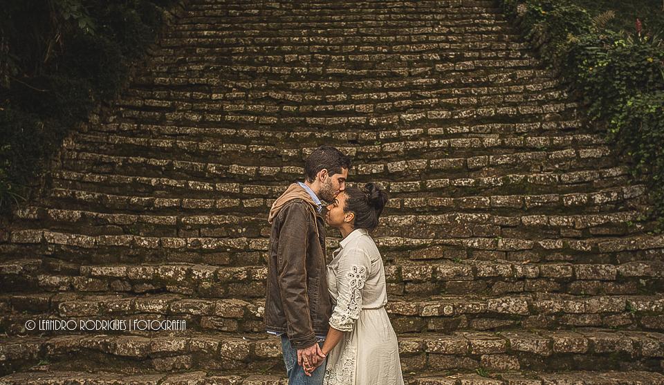 noivos um de frente para o outro de amos dadas, noivo beijando a testa da noiva,de fundo uma escadaria de pedra
