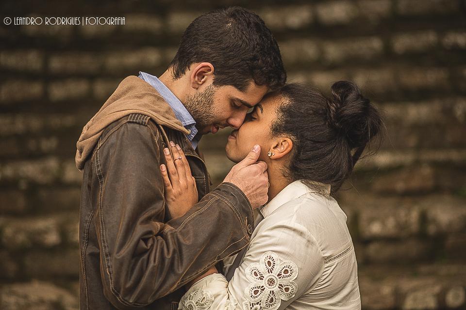 Noivos com as testas encostadas e de olhos fechados, noivo com a mão no rosto da noiva de fundo escadas de pedra