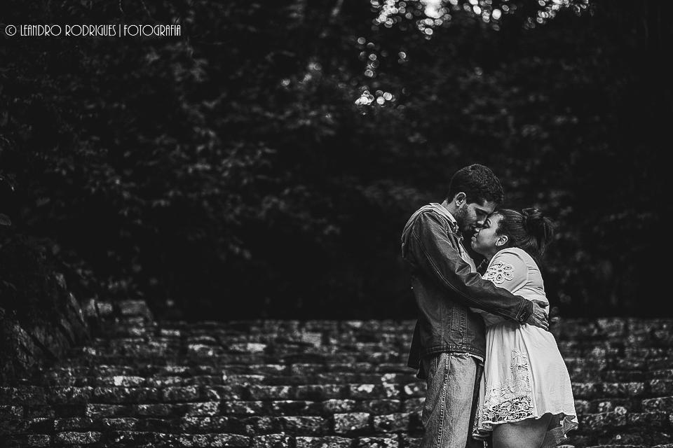 Noivos se abraçando na escada de pedra de fundo arvores