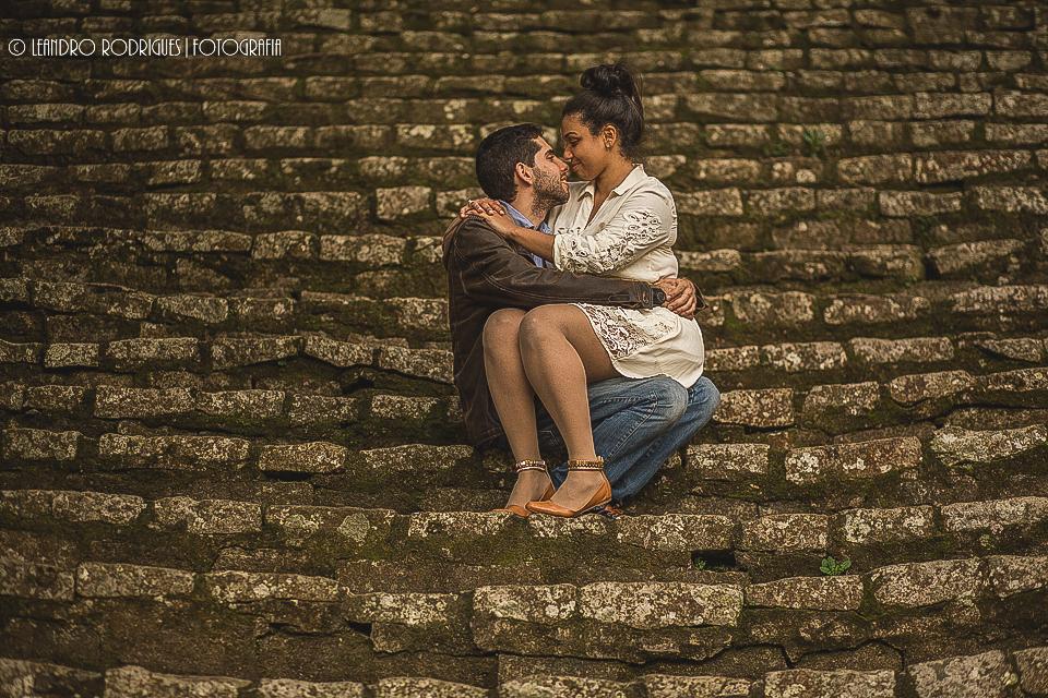 Noivo sentado na escada de pedra e noiva sentada no colo do noivo